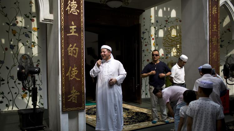 An imam speaks during an Eid al-Fitr prayer session in a mosque in Shanghai