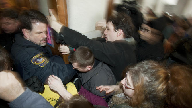 Police try to secure a door during a protest at the Wisconsin state Capitol, Thursday, March 10, 2011, in Madison, Wis. The standoff over union rights that rocked Wisconsin and the nation for weeks headed for a swift end Thursday, as Republican lawmakers were set to strip nearly all collective bargaining rights from the state's public workers and deliver one of the strongest blows to the power of unions in years.  (AP Photo/Morry Gash)