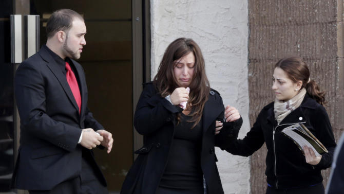 A woman reacts after leaving the church where Jovan Belcher's funeral was held in Dix Hills, N.Y., Wednesday, Dec. 12, 2012. Several hundred mourners have gathered for the funeral of Kansas City Chiefs linebacker Jovan Belcher near his hometown on Long Island. The 25-year-old Belcher shot and killed his girlfriend and then himself Dec. 1. (AP Photo/Seth Wenig)