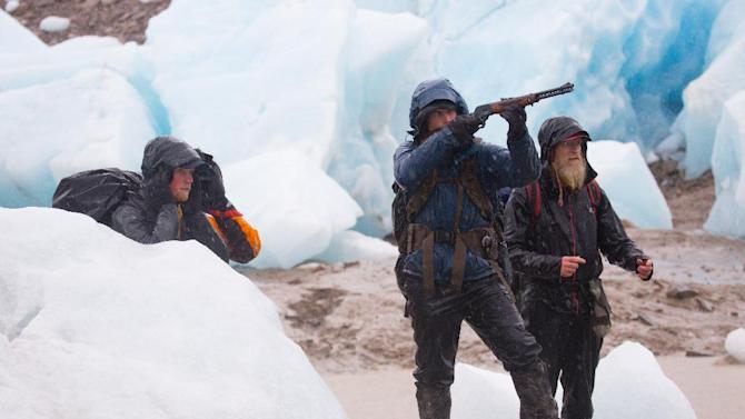 """In this 2012 photo released by National Geographic Channels and Brian Catalina Entertainment, Dallas Seavey, center, shoots at a target as Tyrell Seavey, left, and Willi Prittie watch in Strandline Lake, Alaska. Dallas Seavey, who became the youngest Iditarod champion ever when he won the race in 2012, is among eight mushers or outdoor adventurers featured in the latest reality show set in Alaska. """"Ultimate Survival Alaska"""" premieres Sunday on NatGeoTV. (AP Photo/National Geographic Channels, Stewart Volland)"""