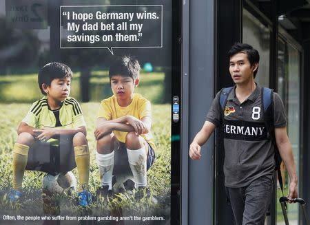 File photo of a man walking past a World Cup anti-gambling advertisement at a taxi stand in Singapore