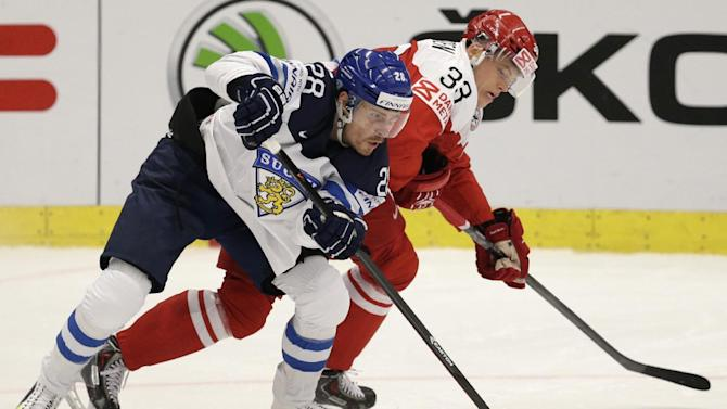 Finland's Anssi Salmela, left, and Denmark's Julian Jakobsen battle for the puck during the Hockey World Championships Group B match in Ostrava, Czech Republic, Sunday, May 3, 2015. (AP Photo/Sergei Grits)