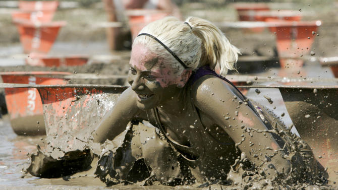 COMMERCIAL IMAGE- In this photograph taken by AP Images for Merrell, a competitor crawls through a mud pit during the Merrell Down & Dirty National Mud and Obstacle Series presented by Subaru, on Sunday, June 24, 2012, at the Aurora Sports Park, near Denver, Colo.. Michael Epstein Sports productions, MESP, will produce 10 Down & Dirty events this summer season alone. (Nathan Bilow /AP Images for Merrell)