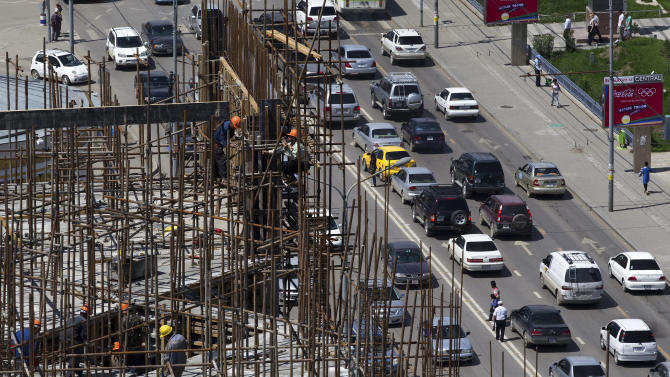 In this July 10, 2012 photo, workers labor at a construction site near the Sukhbaatar Square in Ulan Bator, Mongolia. In the world's rush to get rich off China, Mongolia works mightily to ensure that Chinese investment does not become Chinese dominance. (AP Photo/Andy Wong)