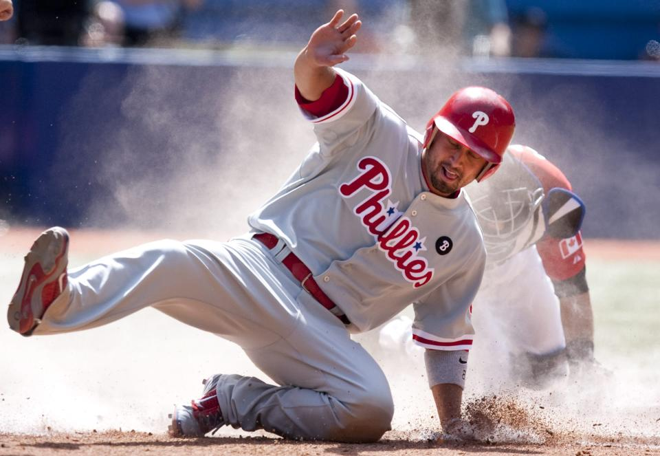 Philadelphia Phillies' Shane Victorino, foreground, scores past Toronto Blue Jays catcher J.P Arencibia after a sacrifice fly from teammate Ben Francisco during the seventh inning of an interleague baseball game, Friday June 1, 2011, in Toronto. (AP Photo/The Canadian Press, Chris Young)