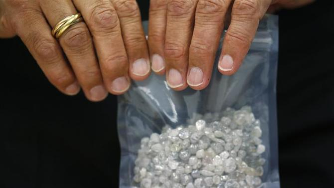 Diamond buyer Elliot Tannenbaum, from the Leo Schachter Diamond Group, holds a bag of uncut diamonds at a sightholders week at De Beers offices in central London