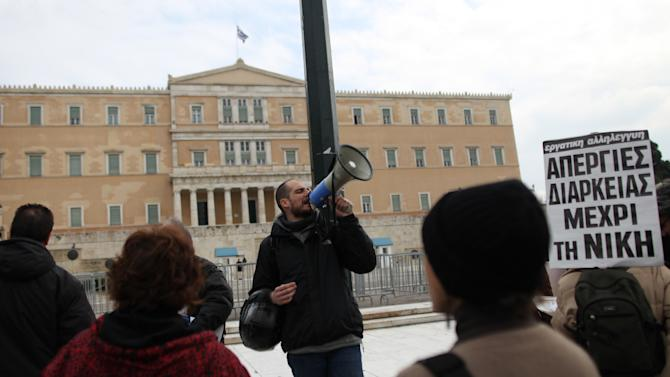 Doctors and health workers protest outside the Greek Parliament in central Athens during a 24-hour strike as a banner reads ''strike until the win'' on Thursday, Feb. 23, 2012. Greek lawmakers on Thursday debated emergency legislation to approve a massive bond swap that would wipe euro107 billion ($142 billion) off the country's privately-held debt, as new projections showed the economy will suffer the worst contraction in Europe this year.(AP Photo/Petros Giannakouris)