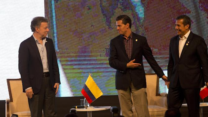 Colombia's President Juan Manuel Santos, left, Mexico's President Enrique Pena Nieto, center, and Peru's President Ollanta Humala, chat during the closing ceremony of the Business Summit in Paracas, Peru, Thursday, July 2, 2015. The Business Summit of the Pacific Alliance is taking place on parallel with the 5th Presidential Pacific Alliance Summit which starts on Friday. (AP Photo/Rodrigo Abd)