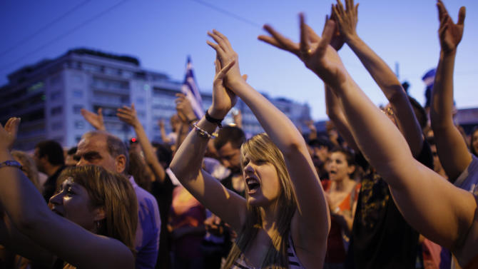 Demonstrators gesture towards the Greek parliament during a peaceful rally in central Athens' Syntagma square, Sunday, June 19, 2011.  Some thousands of protesters have gathered for a 25th consecutive day to protest at fiscal austerity measures and demand that Greece stop paying its debts, and they have denounced politicians of all types as incompetent and corrupt. (AP Photo/Kostas Tsironis)