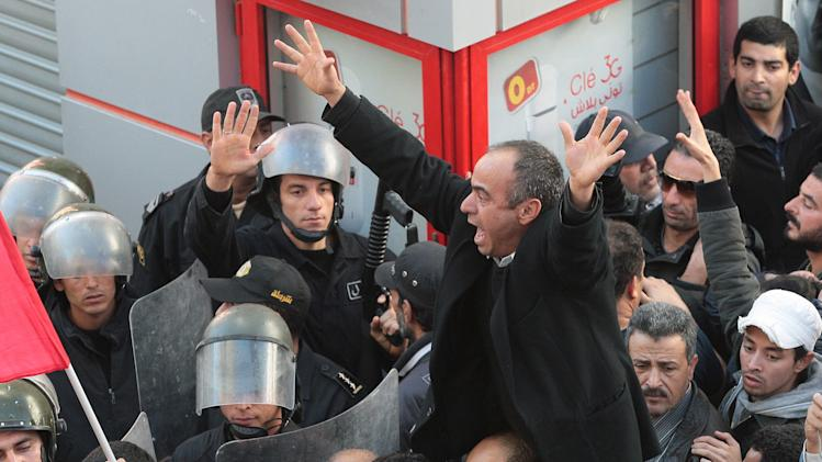 FILE - This Tuesday, Dec. 4, 2012 file photo shows a member of the leftist UGTT union raising his arms next to riot police officers during a rally to commemorate the 1955 assassination of a historic member, before being were attacked by the League for Protection of the Revolution in Tunis, Tunisia. Two years after the revolution that overthrew a dictator and started the Arab Spring, Tunisia is struggling with high unemployment and rising violence in its politics. After sounding the alarm for months over the rise of religious extremists, the opposition now warns that the new threat to this North African country's democratic transition are vigilante bands allied to the elected government.(AP Photo/Amine Landoulsi, File)