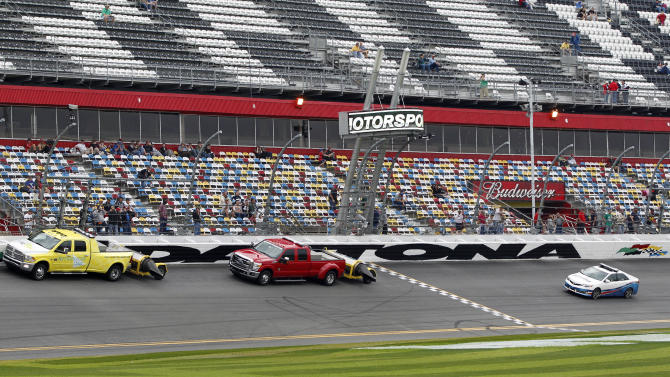 Workers drive jet dryers around the track in an attempt to dry the track as officials drive behind to check conditions at Daytona International Speedway in Daytona Beach, Fla., Monday, Feb. 27, 2012. The NASCAR 500 was postponed from Sunday until Monday because of rain. (AP Photo/Terry Renna)