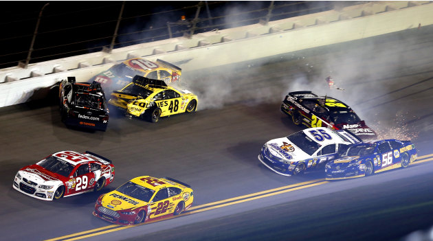 Kevin Harvick (29) and Joey Logano (22) drive away from a wreck involving Denny Hamlin, top left, Jimmie Johnson (48), Kyle Busch (18), Jeff Gordon (24) and Mark Martin (55) in the NASCAR Sprint Unlim