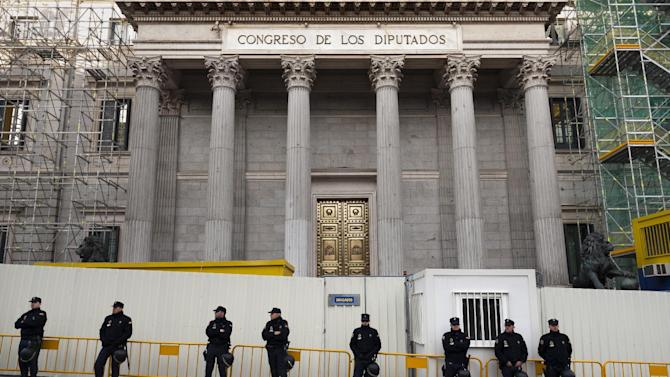 Police officers in riot gear stand guard to prevent demonstrators, some of them from the Platform of People Affected by Mortgages, a group campaigning to stop evictions, from approaching the Parliament as the Spanish Parliament considers whether to admit a popular petition to change mortgage laws and halt evictions of those unable to pay mortgages to a vote in Madrid, Tuesday, Feb. 12, 2013. The government agreed to consider changes to the law on mortgages after pressure from opposition parties and a growing public outcry, including a petition that was signed by 1.4 million people – enough signatures to force Parliament to discuss alterations to the law in a special session. (AP Photo/Daniel Ochoa de Olza)