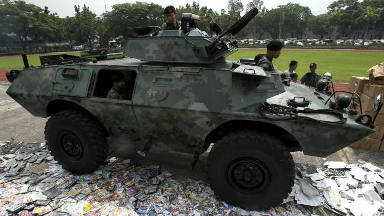 An armored personnel carrier of the Philippine National Police runs over piles of pirated DVDs during a ceremonial destruction of counterfeit goods seized in raids recently at parade grounds of the police headquarters at suburban Quezon city, northeast of Manila, Thursday June 30, 2011. The ceremonial destruction of pirated DVDs and other counterfeit goods was done to coincide with the global celebration and awareness campaign known as World Anti-Counterfeiting Day. (AP Photo/Bullit Marquez)