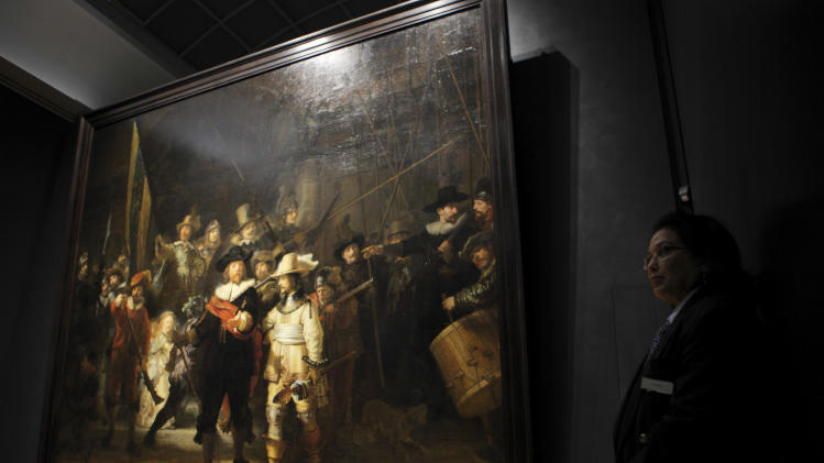 "EXPANDS ORIGINAL CAPTION -- security guard stands next to Rembrandt's ""Night Watch"" painting, illumintaed by newly installed LED lights in Amsterdam, Netherlands, Wednesday Oct. 26, 2011. The ""Night Watch"" may need a different nickname after the painting has been put under new lighting that makes it look like a day scene. The change is startling, as characters once barely visible now stand out in vivid color.  The 1642 painting was commissioned for one of Amsterdam's citizen militias and is officially titled ""The Company of Frans Banning Cocq."" Director Wim Pijbes of the national Rijksmuseum said Wednesday the painting , widely considered Rembrandt's greatest masterpiece, may in fact only have acquired the ""Night Watch"" name due to a dark varnish that was removed decades ago. He said the new LED lighting system custom designed by Philips mimicks daylight, helping return the work to its original dynamic, colorful appearance.  (AP Photo/Peter Dejong)"