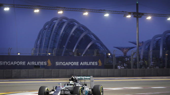 Mercedes driver Lewis Hamilton of Britain steers his car into the pit lane during the first practice session for the Singapore Formula One Grand Prix on the Marina Bay City Circuit in Singapore, Friday, Sept. 19, 2014. (AP Photo/Wong Maye-E)