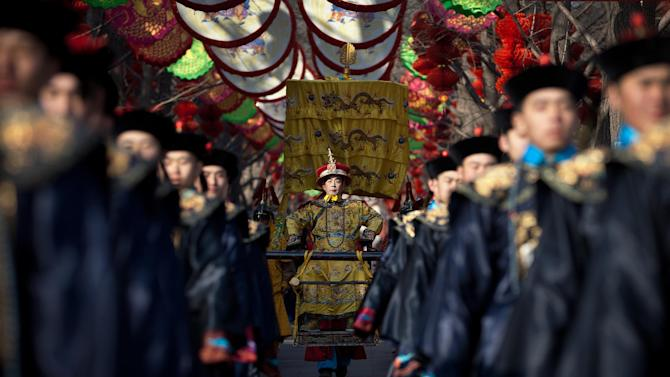 A Chinese actor dressed as Qing Dynasty emperor, center, sits on a sedan chair during a rehearsal of an ancient Qing Dynasty ceremony ahead of the upcoming Chinese New Year at Ditan Park in Beijing Friday, Feb. 8, 2013. Chinese will celebrate the Lunar New Year on Feb. 10 this year which marks the Year of Snake. (AP Photo/Andy Wong)