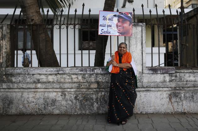 A cricket fan poses for photographers while holding a placard of cricketer Sachin Tendulkar in Mumbai