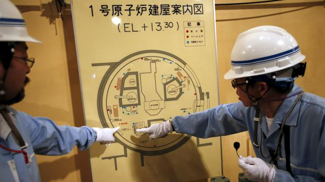 An employee of Kyushu Electric Power Co. speaks to reporters inside No.1 reactor building where fuel rods are being inserted into reactor vessel at Sendai nuclear power station in Satsumasendai