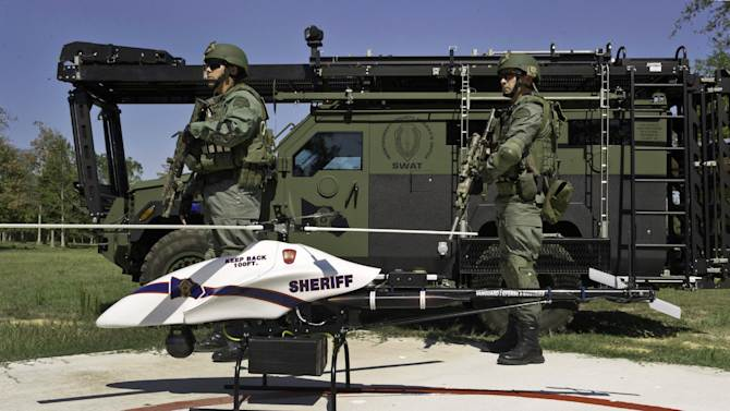 This September 2011 file photo provided by Vanguard Defense Industries, shows a ShadowHawk drone with Montgomery County, Texas SWAT team members. The prospect that thousands of drones could be patrolling U.S. skies by the end of this decade is raising the specter of a Big Brother government that peers into backyards and bedrooms. The worries began mostly on the political margins, but there are signs that ordinary people are starting to fret that unmanned aircraft could soon be circling overhead.  (AP Photo/Lance Bertolino, Vanguard Defense Industries)