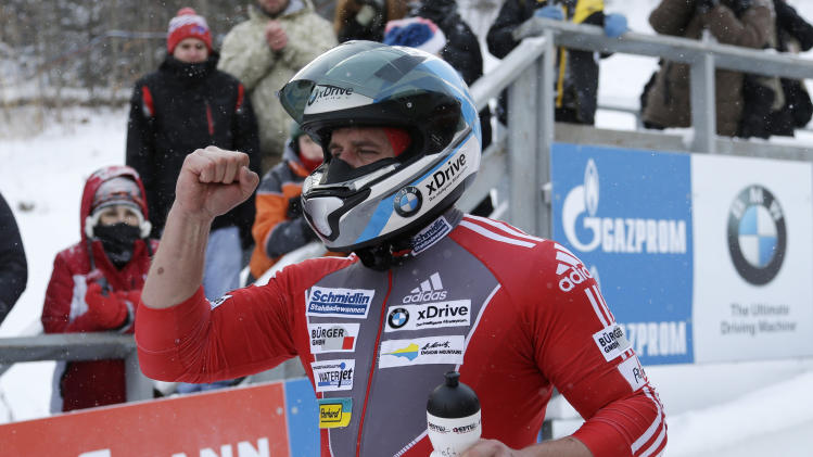 Switzerland's pilot Beat Hefti celebrates after his third-place finish with brakeman Alex Baumann in the two-man bobsled World Cup event on Friday, Dec. 13, 2013, in Lake Placid, N.Y. (AP Photo/Mike Groll)