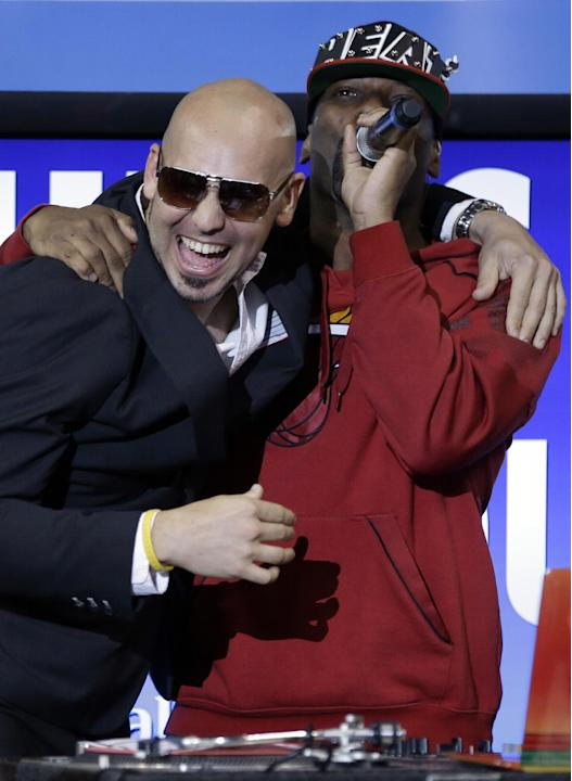 CORRECTS ID TO PITBULL IMPERSONATOR FROM RAPPER PITBULL - Pitbull impersonator, left, hugs DJ Irie, right, during an NBA basketball game between the Miami Heat and Indiana Pacers, Wednesday, Dec. 18,
