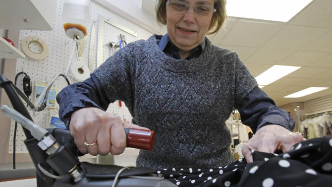 """Judy Anderson irons a dress at the Sewing Basket, Thursday, Feb. 7, 2013, in Montpelier, Vt. When toymaker Hasbro axed the clothes iron token from its Monopoly game at the suggestion of online voters – replacing it with a cat – the company implied that the small household appliance was passe: something your grandmother once used to ease the wrinkles out of socks and handkerchiefs. Even with the rise of """"wrinkle-free,"""" the iron, it seems, is holding its own. While sales in the U.S. declined in volume 1 percent last year, they were up nearly 3 percent overall between 2007 and 2012, according to Euromonitor International. (AP Photo/Toby Talbot)"""