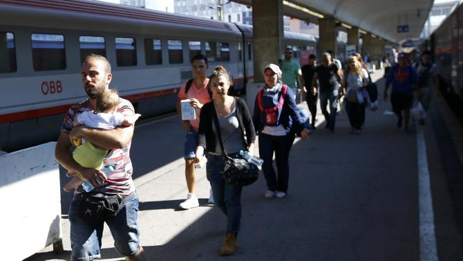 Migrants walk to board a train to Munich at the railway station in Vienna