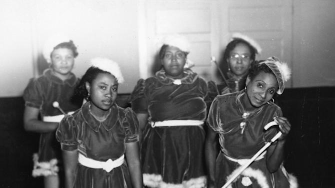 """This 1942 photo provided by the Louisiana State Museum shows Gold Digger Baby Dolls, one of the neighborhood groups that adopted the """"baby doll"""" costumes. The costumes first became part of New Orleans' Mardi Gras in 1912 with a group of black prostitutes, but spread within decades into the city's respectable African-American neighborhoods. The tradition is enjoying a modern resurgence. (AP Photo/State Library of Louisiana, Collection of the U.S. Works Progress Administration of Louisiana)"""