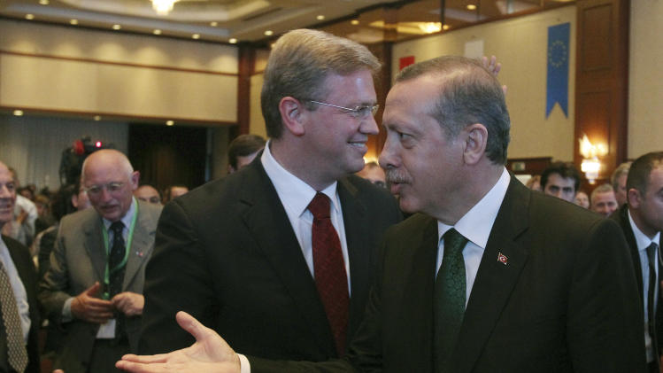 """Turkish Prime Minister Recep Tayyip Erdogan, right, arrives at a conference hall as Stefan Fule, left, the EU enlargement commissioner smiles, in Istanbul on Friday, June 7, 2013. Fule on Friday criticized Turkish police's harsh crackdown on protesters told an audience including Erdogan that a """"swift and transparent"""" investigation was needed. (AP Photo/Thanassis Stavrakis)"""