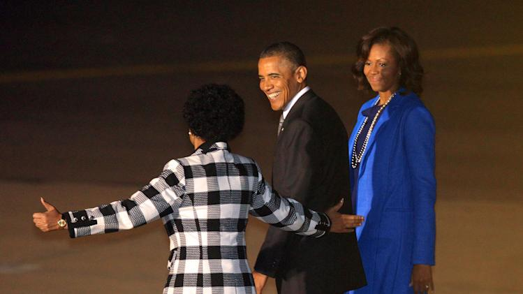 U.S. President Barack Obama, middle, and first lady Michelle Obama, right, react as Maite Nkoana-Mashabane, Minister of International Relations and Cooperation, left, gestures during their arrival at Waterkloof Airbase in Pretoria, Friday, June 28, 2013. President Obama is receiving the embrace you might expect for a long-lost son on his return to his father's home continent, even as he has yet to leave a lasting policy legacy for Africa on the scale of his two predecessors. (AP Photo/Themba Hadebe)