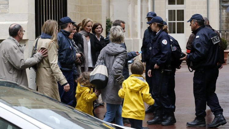 Families arrive at the school after a man committed suicide at a private Catholic school in central Paris by shooting himself in the head, Thursday, May, 16, 2013. The shooting took place shortly before noon as children were leaving the school premises for the lunch break, according to two police officials. Paris Mayor Bertrand Delanoe's office said in a statement that a dozen children witnessed the shooting.(AP Photo/Jacques Brinon)