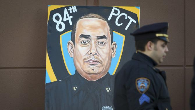 A police officer walks past a painting of NYPD officer Rafael Ramos in his funeral at Christ Tabernacle Church in the Queens borough of New York