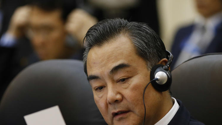 China's Foreign Minister Wang Yi reads a note before the 46th ASEAN Foreign Ministers' Plus Three Meeting to begin in Bandar Seri Begawan, Brunei, Sunday, June 30, 2013. (AP Photo/Vincent Thian)