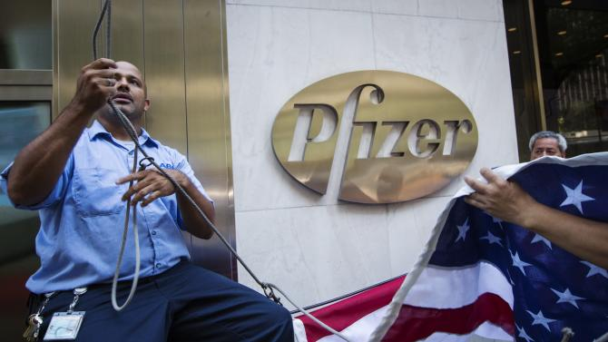 Workers raise a U.S. flag outside the Pfizer building in New York