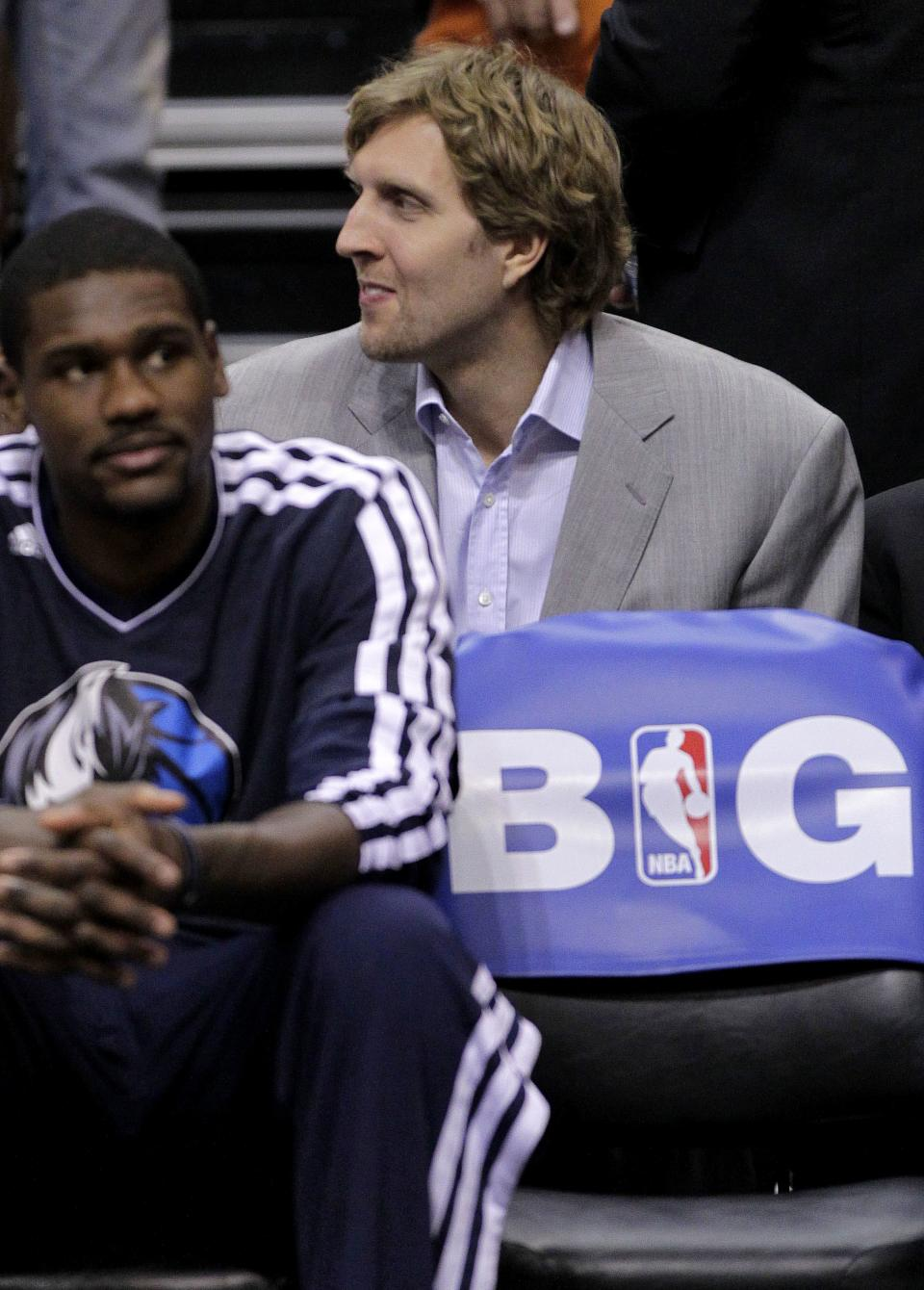 Dallas Mavericks' Dirk Nowitzki watches from the bench against the Phoenix Suns during the second half of an NBA basketball game, Thursday, Dec. 6, 2012, in Phoenix. (AP Photo/Matt York)