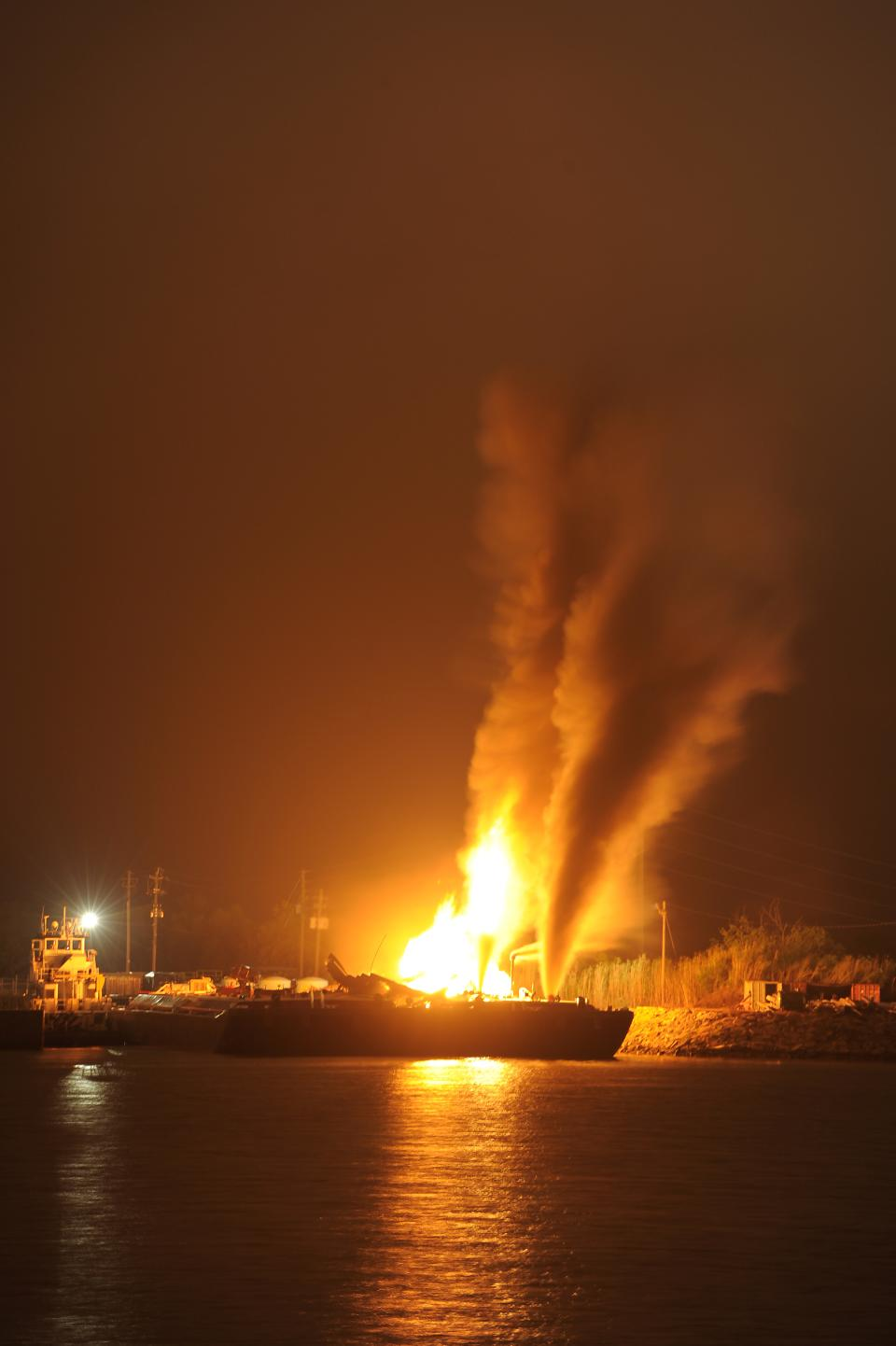 Fire burns aboard two fuel barges along Mobile River after explosions sent three workers to the hospital. Fire officials have pulled units back from fighting the fire due to the explosions and no immediate threat to lives. (AP Photo John David Mercer)