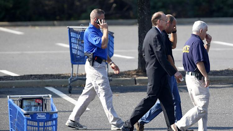 Middlesex County prosecutor Bruce Kaplan, center, walks with officials on the parking lot of a Pathmark grocery store where three people died in an early morning shooting in Old Bridge, N.J., Friday, Aug. 31, 2012.  Officials say a supermarket employee killed two people at the store early Friday and then fatally shot himself. Authorities say he opened fire on employees he saw when he walked into the Pathmark store. The store's front windows were shattered by gunfire.  The motive is being investigated. (AP Photo/Julio Cortez)