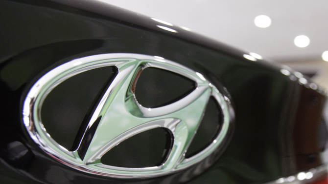 FILE - In this July 26, 2012 file photo, the logo of Hyundai Motor Co. is seen on its car at the company's showroom in Seoul, South Korea.  Hyundai Motor Co. is recalling some Santa Fe SUVs and Sonata sedans because of problems with their air bags. The Santa Fe recall involves nearly 200,000 vehicles in the 2007 to 2009 model years. Hyundai dealers will reprogram the front passenger air bag sensors so they will accurately detect when a small adult is seated. (AP Photo/Ahn Young-joon, File)