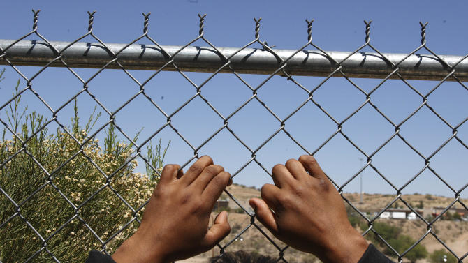 FILE - In this May 18, 2006 file photo, a man rests his hands on a fence looking out to the United States from a Mexican customs station after being detained by U.S. Border Patrol in Arizona and returned to Mexico in Nogales, Mexico. The border near Nogales is consider the nation's busiest illegal corridor. (AP Photo/Gregory Bull)
