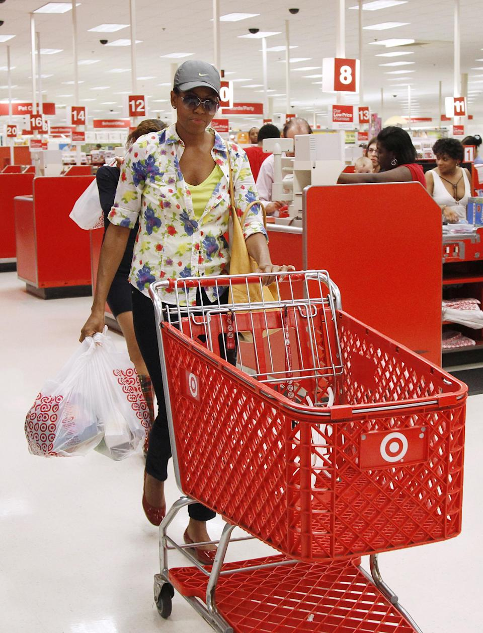 First lady Michelle Obama, wearing a hat and sunglasses, pushes a shopping cart as she carries her purchases at a Target department store in Alexandria, Va., Thursday, Sept. 29, 2011, after doing some shopping. (AP Photo/Charles Dharapak)