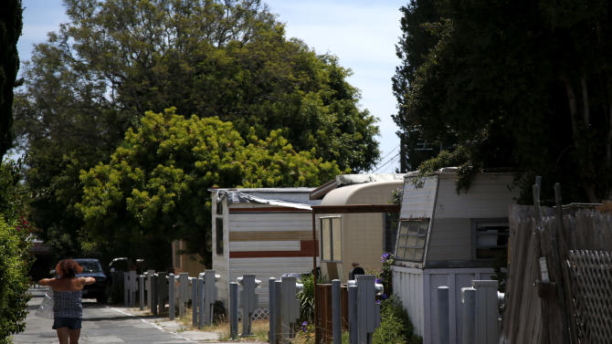 A woman walks past mobile homes at the Santa Monica Village Trailer Park in Santa Monica, Calif., Tuesday, July 10, 2012. The city's Planning Commission recently recommended the 3.8-acre park's zoning be changed to allow a developer to bulldoze its modest, rent-controlled homes and replace them with nearly 200 much-higher-priced apartments and condominiums, as well as more than 100,000 square feet of office and retail space. (AP Photo/Jae C. Hong)