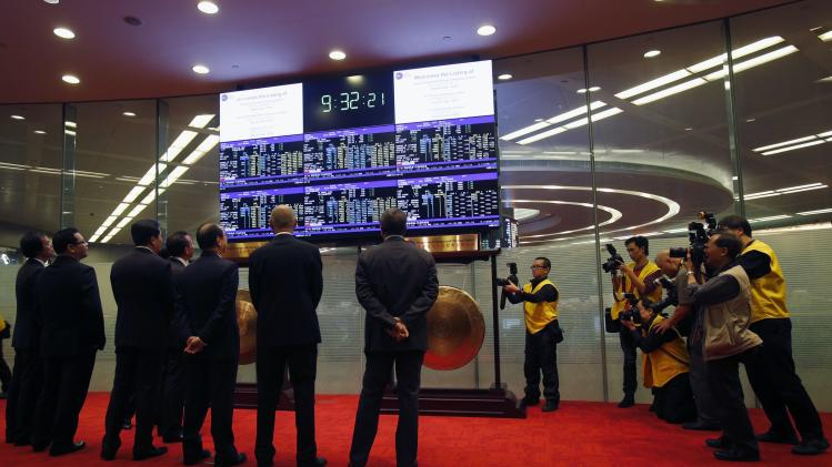 Top executives from six companies, including China Everbright Bank, and representative from the Hong Kong Stock Exchange, watch panel displaying share prices during debut at Hong Kong Stock Exchange