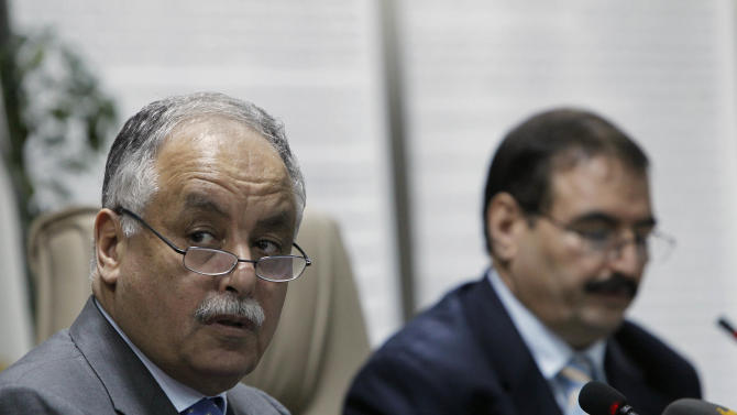 """In this photo taken on a government-organized tour, Libyan Prime Minister Al-Baghdadi al-Mahmoudi, left, and Oil Minister Omran Bokraa listen during a press conference at the Oil Ministry in Tripoli, Libya, Thursday, July 14, 2011.  Libya's prime minister says the government has barred Italy from participating in his country's oil sector, citing Rome's role in the NATO airstrikes on the North African nation. Al-Mahmoudi, however, left the door open for other countries to continue their operations in Libya's vital oil sector as long as they """"reviewed"""" their participation in the alliance's airstrikes, which are targeting forces loyal to Libyan leader Moammar Gadhafi. (AP  Photo/Tara Todras-Whitehill)"""