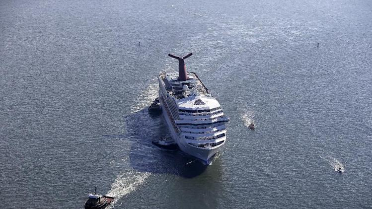 FILE - This Feb. 14, 2013 file photo shows the disabled Carnival Lines cruise ship Triumph being towed to harbor off Mobile Bay, Ala.  Carnival Cruise Lines prices have taken a dip this spring, according to pricing data, and some industry observers are blaming headlines over problems on several Carnival ships. The fares on this trip and some others began to sink following headlines about an engine fire that knocked out power on the Carnival Triumph in mid-February. Passengers endured filthy conditions as the trip was towed to Mobile, Ala., resurrecting stories of a similar incident from 2010 aboard the Carnival Splendor. (AP Photo/Gerald Herbert, file)