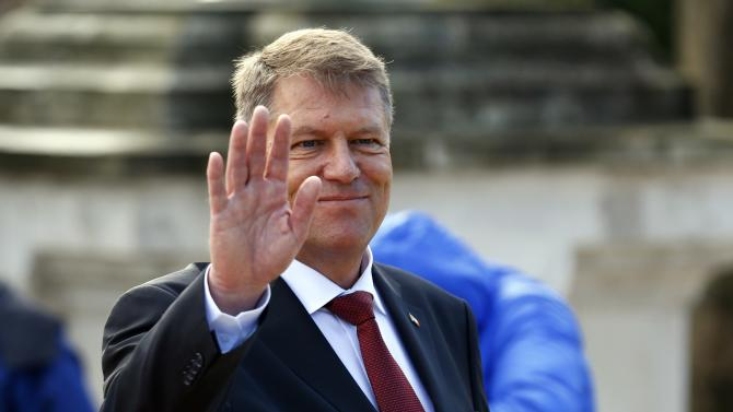 Romania's new President Iohannis gestures to the media during a take-over ceremony at Cotroceni presidential palace in Bucharest