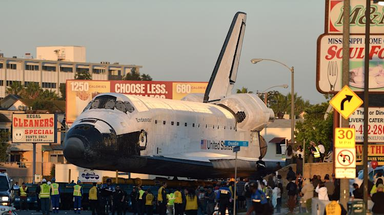 "Space Shuttle Endeavour makes it's way down Manchester Blvd in Inglewood, Calif., Saturday, Oct. 13, 2012.  The Endeavour's terrestrial journey began before dawn Friday when it departed from the Los Angeles International Airport, rolling on a 160-wheeled carrier past diamond-shaped ""Shuttle Xing"" signs. Over two days, it will trundle 12 miles (19 kilometers) at a top speed of 2 mph (3 kph) to its final destination, the California Science Center where it will be the centerpiece of a new exhibit. (AP Photo/Los Angeles Newspaper Group, Jeff Gritchen, Pool)"