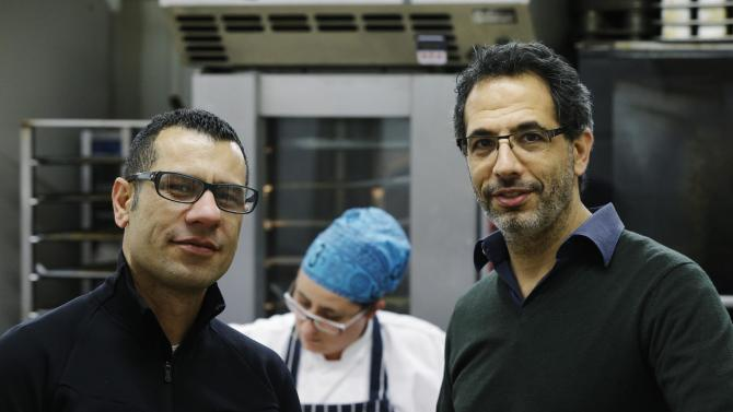 In this Tuesday, Dec. 18, 2012 photo, chefs Yotam Ottolenghi, right, and Sami Tamimi, left, pose for the photographer at their company's bakery in London. One chef is Israeli, the other a Palestinian. So it is with 'Jerusalem' their latest cookbook, that traces their memories of a shared city, the Jewish west and the Arab east, together with the food_ the commodity held in common in a city riven by division. Ottolenghi and Tamimi who have been business partners for about 10 years, run two restaurants and three delis in London and wrote their first cookbook four years ago. They were simply known for saving London's chicest neighborhoods from culinary boredom with Mediterranean-based recipes infused with exotic flavors.  Their new book 'Jerusalem' explores  the cuisine of the ancient city. (AP Photo/Lefteris Pitarakis)