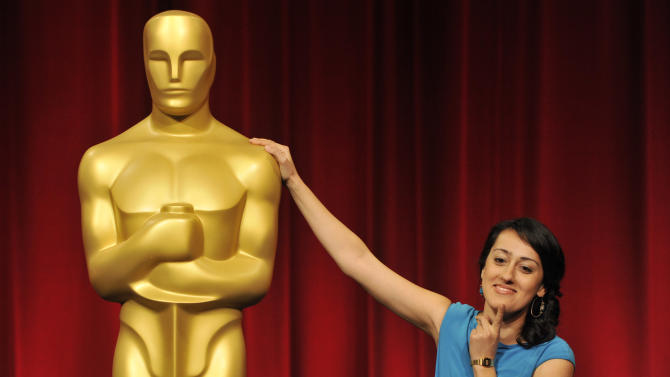 """Filmmaker Talkhon Hamzavi of Zurich University of the Arts in Switzerland, a nominee in the Foreign Film Category for her film """"Parvaneh,"""" poses alongside an Oscar statue before the Academy of Motion Picture Arts and Sciences 40th Student Academy Awards at the Samuel Goldwyn Theater on Saturday, June 8, 2013 in Beverly Hills, Calif. (Photo by Chris Pizzello/Invision/AP)"""