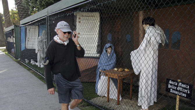 "FILE - In this Dec. 13, 2011 file photo, a man walks past two of the traditional Nativity scenes along Ocean Avenue at Palisades Park in Santa Monica, Calif. Avowed atheist Damon Vix last year won two-thirds of the booths in the annual, city-sponsored lottery to divvy up spaces in the live-sized Nativity display.  But he only put up one thing: A sign that read ""Religions are all alike - founded on fables and mythologies."" Vix left the rest of his allotted spaces empty, and in so doing, upended a Christmas tradition that began in Santa Monica nearly 60 years ago. (AP Photo/Ringo H.W. Chiu, file)"